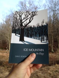 Holding a copy of Ice Mountain against the trees