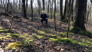 man sitting in woods