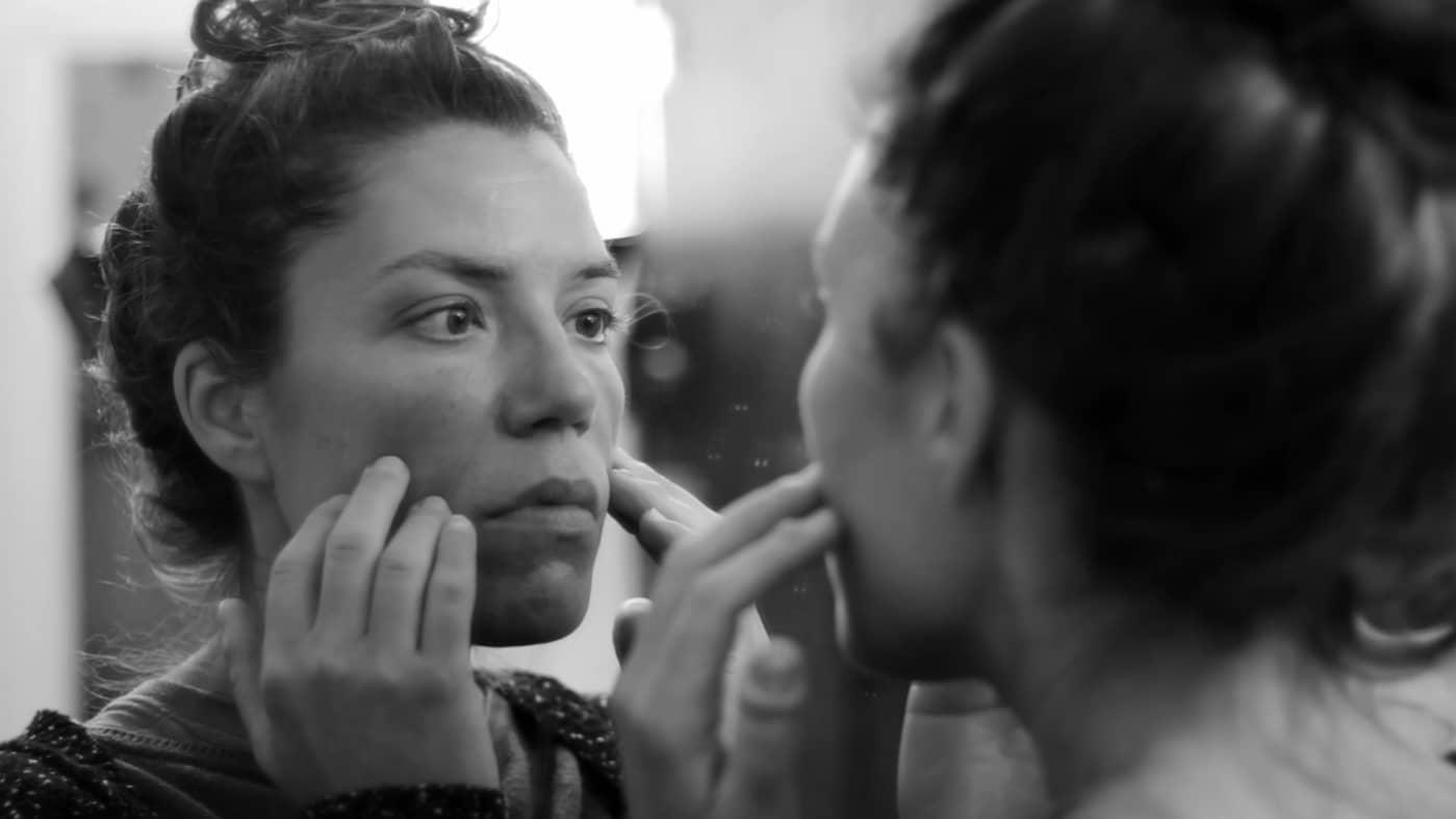 screenshot from Estado Fallido showing a woman examining her face in the mirror